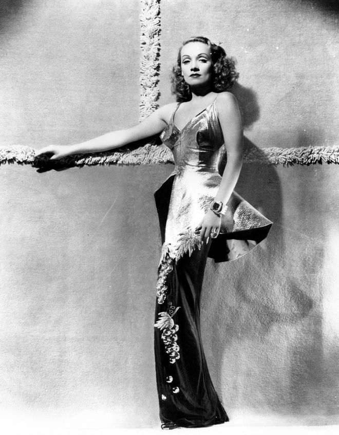 This is a 1940 photo of actress and entertainer Marlene Dietrich wearing a gold lame and black silk taffeta wardrobe in Hollywood, Calif.  (AP Photo)