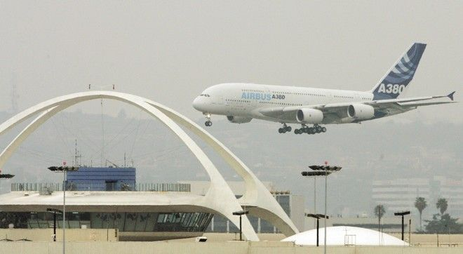 An Airbus A380, the world's largest passenger jet, passes the Los Angeles International Airport Theme building as it prepares to touch down on the inaugural visit of the superjumbo jet to Los Angeles, Monday, March 19, 2007.   (AP Photo/Reed Saxon)
