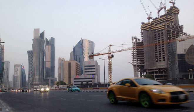FILE - In this Monday, July 10, 2017 file photo, a sports car drives through downtown Doha. Its been more than a month since four Arab nations cut land, sea and air routes to Qatar, but in the gas-rich Gulf nations glimmering malls and luxury hotels there is little sign of hardship. (AP Photo/Maggie Hyde, File)