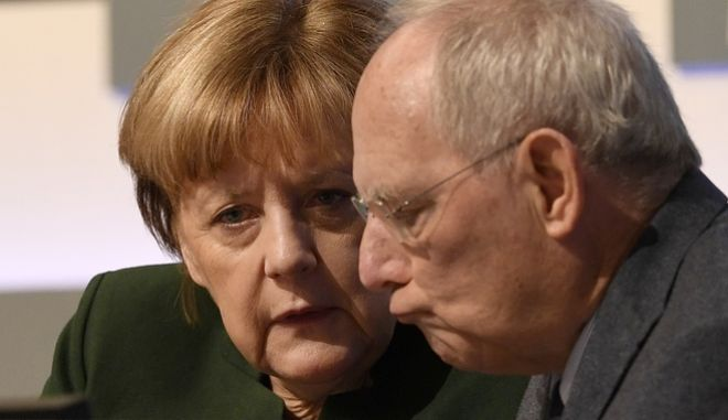 German Chancellor Angela Merkel, left, talks to German Finance Minister Wolfgang Schaeuble at the general party conference of the Christian Democratic Union (CDU) in Essen, Germany, Wednesday, Dec. 7, 2016. Merkel has won a new term as the leader of Germany's main conservative party after stressing her determination to prevent a repeat of last year's huge migrant influx and advocating a partial ban on face-covering veils. (AP Photo/Martin Meissner)