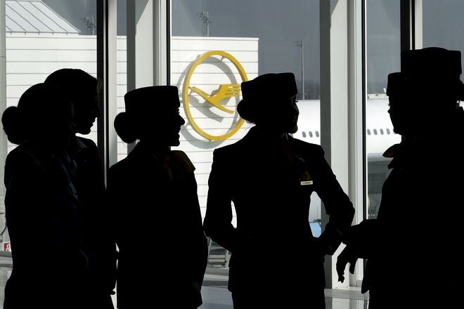 Lufthansa flight attendants silhouetted as they pose for a photograph on occasion of the company's annual press conference in Munich, Germany, Thursday, March 16, 2017. (AP Photo/Matthias Schrader)