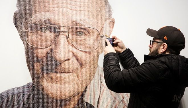 A visitor takes a photo of founder of Swedish multinational furniture retailer IKEA, Ingvar Kamprad, at the IKEA museum, in Almhult, Sweden, on Sunday Jan. 28, 2018. The portrait of Kamprad on the wall is made out of a big amount of small portraits of employees. Kamprad died Saturday Jan. 27, aged 91. (Ola Torkelsson/TT via AP)