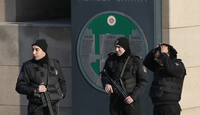 Turkish police officers guard a court in Istanbul, Wednesday, Jan. 31, 2018, with sign reading in Turkish: 'Justice Palace'.  Turkey's state-run news agency Anadolu Agency says Wednesday the court has sentenced three people to life prison terms for their involvement in an Islamic State group suicide bomb attack in Jan. 2016 at Istanbul's historic Sultanahmet district that killed 12 German tourists and wounded 15 people, including nine Germans and citizens of Norway, Peru and South Korea. (AP Photo/Lefteris Pitarakis)