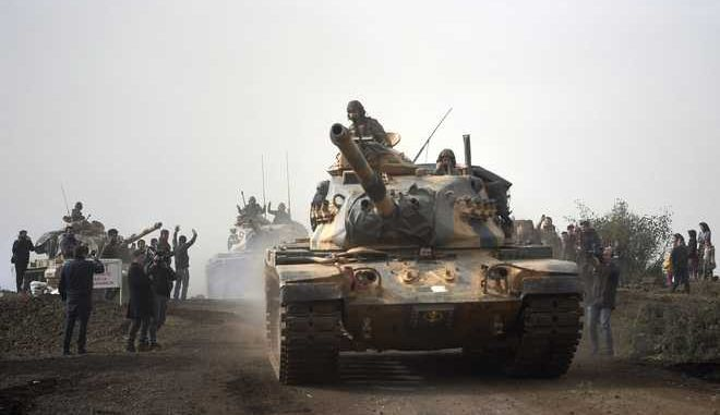 "Turkish army tanks enter Afrin, an enclave in northern Syria controlled by U.S.-allied Kurdish fighters, in Hassa, Hatay, Turkey, Monday, Jan. 22, 2018. Turkey's President Recep Tayyip Erdogan has said his country will ""not take a step back"" from its military operation on Afrin. Speaking in Ankara on Monday - the third day of the operation Erdogan said Turkey's ""fundamental goal"" is ensuring national security, preserving Syria's territorial integrity and protecting the Syrian people.(AP Photo)"