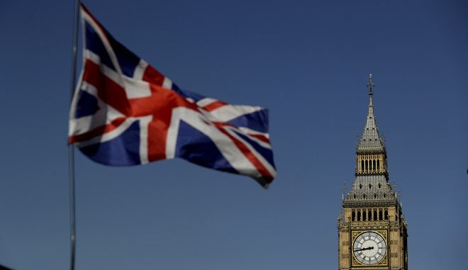 A British Union flag flies above a stand selling tourist souvenirs backdropped by the Houses of Parliament in London, Monday, June 19, 2017. After almost a year of waffling, Britain finally opens negotiations with its European Union counterparts on Monday about leaving the bloc. (AP Photo/Matt Dunham)