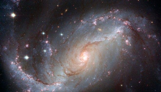 Στον ραβδωτό σπειροειδή γαλαξία NGC 1672, φαίνονται σμήνη από νεαρά θερμά, μπλε, αστέρια κατά μήκος των σπειρών του, καθώς και νέφη υδρογόνου που ακτινοβολούν στο κόκκινο