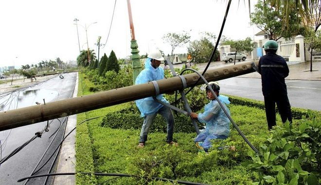 Workers repair a fallen electricity pole in the central province of Phu Yen, Vietnam, Saturday, Nov. 4, 2017. Typhoon Damrey slammed the south central coast of Vietnam on Saturday killing one person and leaving five others missing.(The Lap/Vietnam News Agency via AP)