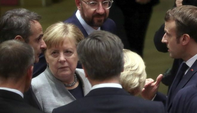 German Chancellor Angela Merkel, third left, speaks with Greek Prime Minister Kyriakos Mitsotakis, left, and French President Emmanuel Macron, right, during an EU summit in Brussels, Friday, Feb. 21, 2020. Major contributors to the European Union's budget blocked progress at an emergency summit on Friday, insisting that they would not stump up more funds for the bloc's next long-term spending package. (Yves Herman, Pool Photo via AP)