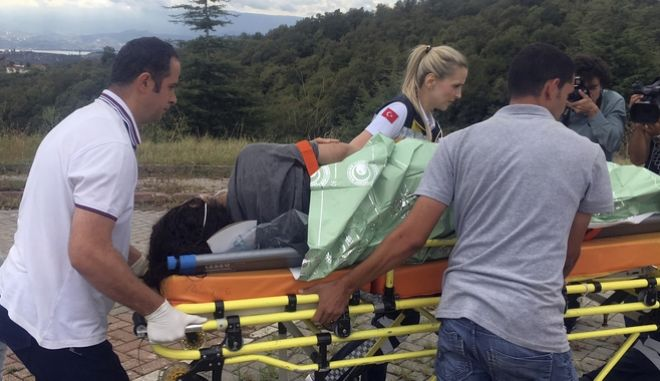 Turkish medics carry a survivor from a capsized ship to a hospital in Kocaeli, Turkey, Friday, Sept. 22, 2017. A fishing boat carrying migrants sank off Turkey's coast in the Black Sea early Friday, killing more than 10 and leaving others missing, the Turkish coast guard said. At least 40 migrants were rescued by coast guard boats and commercial ships, the Coast Guard Command said in a statement. (DHA-Depo Photos via AP)