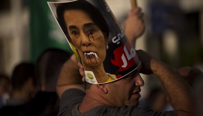 """A member of the Islamic Movement in Israel, a political movement for Arab Muslims inside Israel, displays a defaced poster of Myanmar's State Counsellor Aung San Suu Kyi during a demonstration to condemn Myanmar's treatment of the Muslim Rohingya minority, in front of the embassy of Myanmar, in Tel Aviv, Israel, Monday, Sept. 11, 2017. Protest leader Ibrahim Sarsour said the crowd came to condemn what he called """"atrocities"""" committed by the Myanmar government. (AP Photo/Oded Balilty)"""