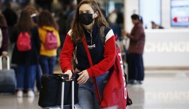 Γυναίκα με μάσκα στο αεροδρόμιο