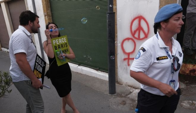 """Διαδηλωτής για την ειρήνη φυσά μπουρμπουλήθρες σε αστυνομικό των Ηνωμένων Εθνών που βρίσκεται στην """"νεκρή ζώνη"""" που χωρίζει την Λευκωσία της Κύπρου"""