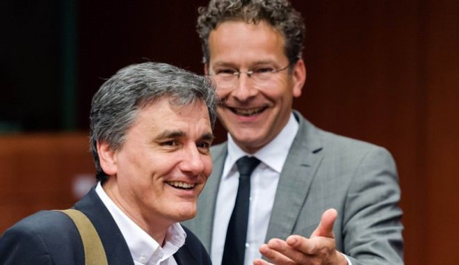 Dutch Finance Minister and chair of the eurogroup finance ministers Jeroen Dijsselbloem, right, smiles as he arrives with Greece's Finance Minister Euclid Tsakalotos for an EU eurogroup meeting at the EU Council building in Brussels on Monday May 9, 2016. European finance ministers gathered in Brussels Monday for talks aimed at breaking the deadlock over whether to provide more aid to bolster Greece's shattered economy and forgive some of its debts. (AP Photo/Geert Vanden Wijngaert)