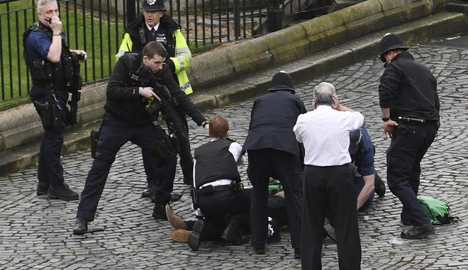 """A policeman points a gun at a man on the floor as emergency services attend the scene outside the Palace of Westminster, London, Wednesday, March 22, 2017.  London police say they are treating a gun and knife incident at Britain's Parliament """"as a terrorist incident until we know otherwise."""" The Metropolitan Police says in a statement that the incident is ongoing. It is urging people to stay away from the area. Officials say a man with a knife attacked a police officer at Parliament and was shot by officers. Nearby, witnesses say a vehicle struck several people on the Westminster Bridge.  (Stefan Rousseau/PA via AP)."""