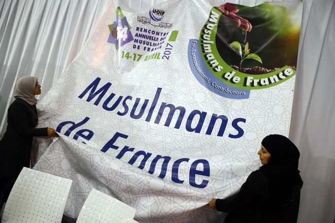 "Women help to adjust a banner reading ""Muslims of France"" inside an exhibition hall at the France Muslim Annual Fair in Le Bourget, north of Paris, Saturday, April 15, 2017. Tens of thousands of Muslims are expected at the three-day event this weekend organized by the ultra-conservative Union of Islamic Organizations of France. It includes merchant stalls, Quran readings, prayers and speeches by leading Muslim figures as Muslims of France want to make sure their voices are heard in France's presidential elections. (AP Photo/Francois Mori)"