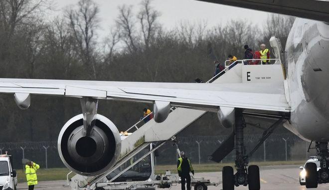 Επιβάτες αποβιβάζονται από  αεροπλάνο που μεταφέρει Βρετανούς υπηκόους από την πόλη του Wuhan στην Κίνα