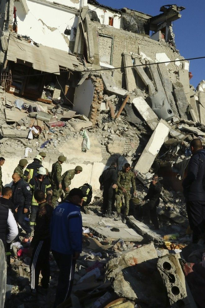 Rescuers search at a damaged building after a magnitude 6.4 earthquake in Thumane, western Albania, Tuesday, Nov. 26, 2019. Rescue crews used excavators to search for survivors trapped in toppled apartment buildings after a powerful pre-dawn earthquake in Albania killed at least six people and injured more than 300. (AP Photo/Hektor Pustina)