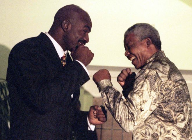 The triple world heavyweight boxing champion, Evander Holyfield (L) and South African President Nelson Mandela face each other at Presidential residence in Johannesburg July 7. Holyfield on a short visit to South Africa, sponsored by Coca-Cola, visited President Mandela who leaves for an official visit to the United Kingdom tonight accompanied by Graca Machel.  SAFRICA HOLYFIELD - RTR58CG