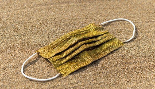 Μάσκα κορονοϊού σε χρυσό χρώμα (φωτογραφία αρχείου)