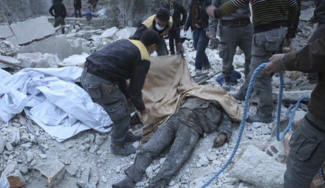 This photo released Feb. 20, 2018 by the Syrian Civil Defense group known as the White Helmets, shows members of the Syrian Civil Defense group removing a victim from under the rubble of a damaged shelter that was attacked during airstrikes and shelling by Syrian government forces, in Ghouta, a suburb of Damascus, Syria. Thousands of Syrians huddle in basements and underground shelters across eastern Ghouta, outside Damascus, hiding from the horror raining down from Syrian army jets that almost never leave the skies. (Syrian Civil Defense White Helmets via AP)