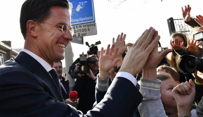 Dutch Prime Minister Mark Rutte gives 'high five' to children after casting his vote for the Dutch general election in The Hague, Netherlands, Wednesday, March 15, 2017. (AP Photo/Patrick Post)