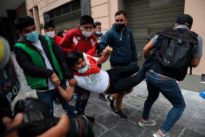Η αστυνομία με πολιτικά ρούχα κρατεί έναν υποστηρικτή του πρώην Προέδρου Martin Vizcarra καθώς αυτός και άλλοι διαδηλωτές αποκλείονται από το να φτάσουν στο Κογκρέσο για να διαμαρτυρηθούν ενάντια στην ορκωμοσία του Μανουέλ Μερίνο