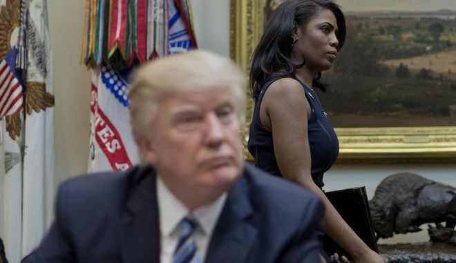 White House Director of communications for the Office of Public Liaison Omarosa Manigault, right, walks past President Donald Trump during a meeting on healthcare in the Roosevelt Room of the White House in Washington, Monday, March 13, 2017. (AP Photo/Pablo Martinez Monsivais)