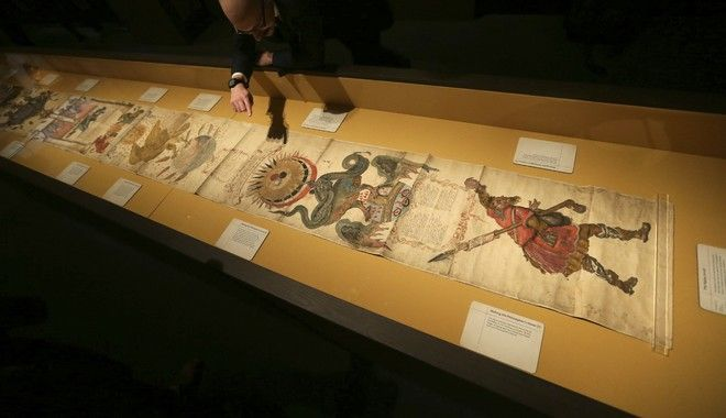 A member of British Library staff poses for a picture pointing at the Philosopher's Stone on the 16th-century Ripley Scroll, which describes how to make a Philosopher's Stone, at the