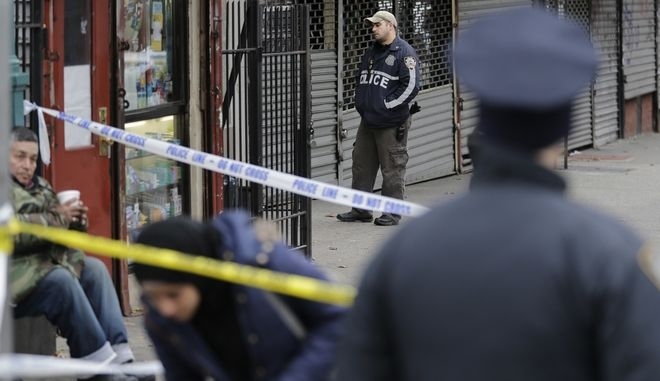 As police officers stand nearby, pedestrians make their way through crime scene tape at the scene of a shooting in the Bronx section of New York, Tuesday, Dec. 5, 2017. New York City police say an officer has fatally shot a man who refused to drop a large knife. (AP Photo/Seth Wenig)