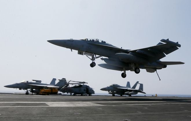 A U.S. Navy F-18 fighter jet lands on the deck of the USS Carl Vinson (CVN 70) aircraft carrier following a routine patrol off the disputed South China Sea, Friday, March 3, 2017. The U.S. military took journalists Friday to the carrier while on patrol off the disputed South China Sea, sending a signal to China and American allies of its resolve to ensure freedom of navigation and overflight in one of the world's security hotspots. (AP Photo/Bullit Marquez)
