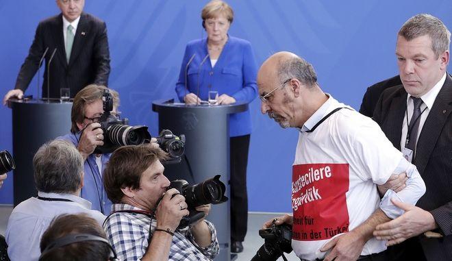 Διαμαρτυρόμενος δημοσιογράφος συνοδεύεται έξω από την αίθουσα όπου λαμβάνει χώρα η συνέντευξη Τύπου Ερντογάν και Μέρκελ στο Βερολίνο. Ο τουρκικής καταγωγής άνδρας φορούσε μπλούζα όπου αναγραφόταν «Ελευθερία στους δημοσιογράφους»
