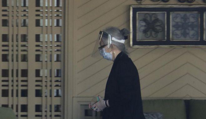 Γυναίκα με προστατευτική μάσκα για τον ιό.