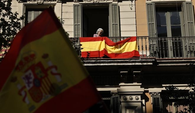 A woman places a Spanish flag on a balcony during a mass rally against Catalonia's declaration of independence, in Barcelona, Spain, Sunday, Oct. 29, 2017. Thousands of opponents of independence for Catalonia are holding the rally on one of the city's main avenues after one of the country's most tumultuous days in decades. (AP Photo/Gonzalo Arroyo)