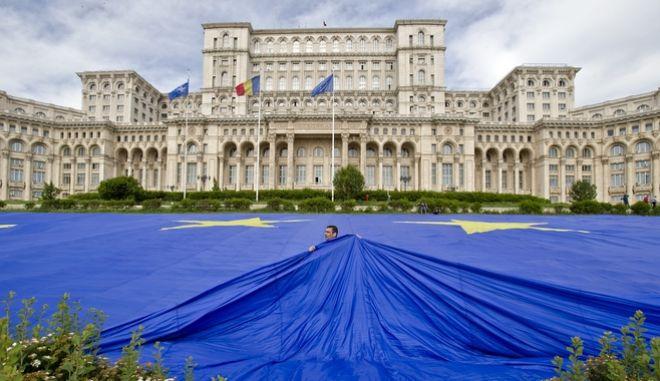 Εργάτης τοποθετεί μια τεράστια σημαία της Ε.Ε. έξω από τη Βουλή στο Βουκουρέστι