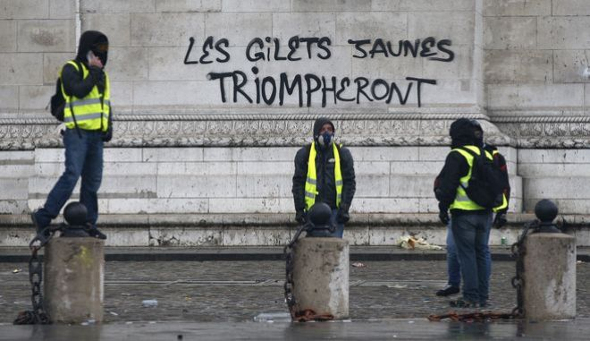 """Διαδηλωτές στο Παρίσι κατά τη διάρκεια των επεισοδίων. """"Τα Κίτρινα γιλέκα θα θριαμβεύσουν"""" γράφει το σύνθημα."""