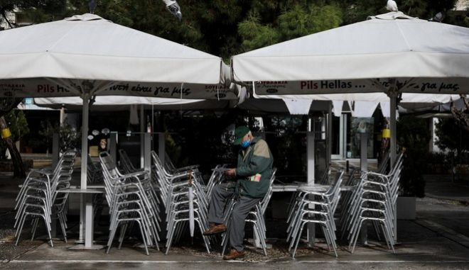 Άνδρας με μάσκα μπροστά από κλειστή επιχείρηση λόγω lockdown.