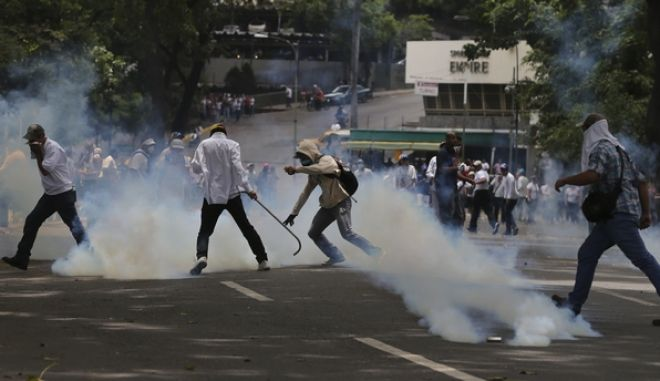 Demonstrators run for cover from tear gas launched by security forces during an anti-government protest in in Caracas, Venezuela, Wednesday, April 19, 2017. Opponents of President Nicolas Maduro called on Venezuelans to take to the streets in marched against the embattled socialist leader. Government supporters are holding their own counter demonstration. (AP Photo/Fernando Llano)