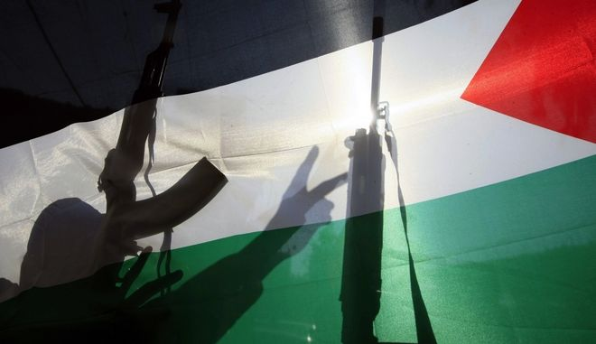 The shadow of a gunman from the Popular Front for the Liberation of Palestine is cast on a Palestinian flag as he flashes the victory sign, in the Ein el-Hilweh Palesinian refugee camp near Sidon, Lebanon, Tuesday, Nov. 18, 2014, to celebrate an attack on a synagogue in Jerusalem. Two Palestinian cousins armed with meat cleavers and a gun stormed a Jerusalem synagogue during morning prayers killing four people in the city's bloodiest attack in years. Police killed the attackers in a shootout. (AP Photo/Mohammed Zaatari)