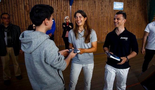 Ο Χρήστος Βολικάκης και η Βασιλεία Καραχάλιου, μοιράζουν αθλητικό υλικό της Stoiximan στους μαθητές της Ελευσίνας.