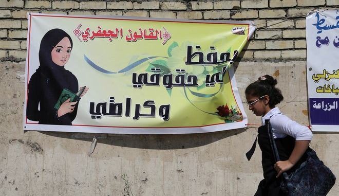 """In this Thursday, March 13, 2014 photo, a schoolgirl passes by a banner for the Jaafari Personal Status Law in Baghdad, Iraq. The Arabic on the banner reads, """"the Jaafari Personal Status Law saves my rights and my dignity."""" A contentious civil status draft law for Iraqi Shiite community that allows child marriage and restricts womens rights has stirred up a row among many Iraqis who see it as a setback for child and women rights, threatening to add more divisions and woos to the society that is already in fragments. (AP Photo/Karim Kadim)"""