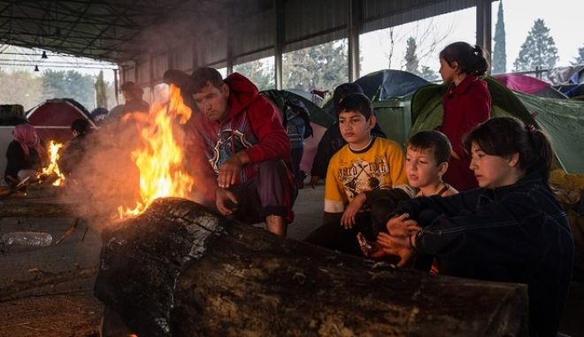 A migrants family stay warm near a fire inside an abandoned train workshop that is used by migrants as a temporary shelter, near the village of Idomeni, Greece on March 12, 2016.
