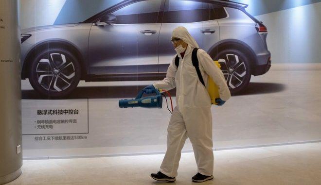 Υπάλληλος που κάνει απολύμανση στο Πεκίνο.