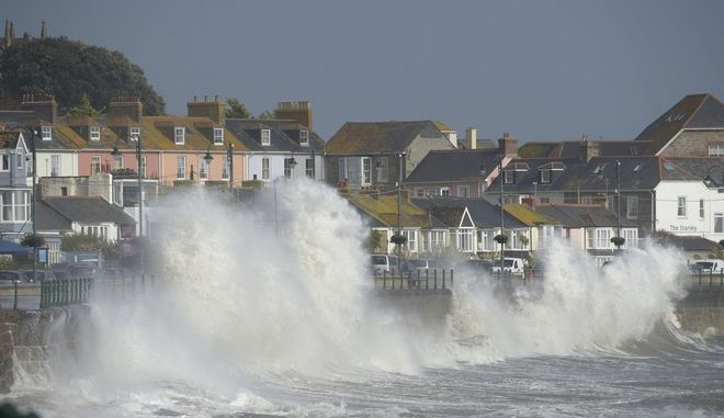 Waves break on the sea wall at Penzanze, southwestern England, as the remnants of  Hurricane Ophelia begins to hit parts of Britain and Ireland. Ireland's meteorological service is predicting wind gusts of 120 kph to 150 kph (75 mph to 93 mph), sparking fears of travel chaos. Some flights have been cancelled, and aviation officials are warning travelers to check the latest information before going to the airport Monday.  (Ben Birchall/PA via AP)