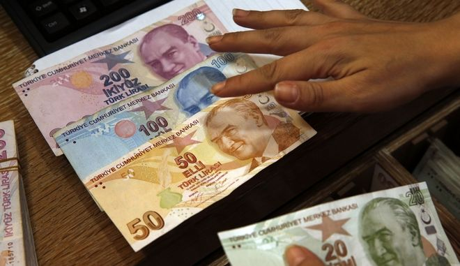 FILE- In this Wednesday, Aug. 15, 2018, file photo a worker at a currency exchange shop exhibits Turkish lira banknotes bearing pictures of modern Turkey's founder Mustafa Kemal Ataturk, in Istanbul. Investors have been pulling out of Turkeys markets, sending its stock market and currency plunging. Thats making debt that Turkish companies owe in dollar terms even more expensive to pay back, which only further weakens the countrys financial system. (AP Photo/Lefteris Pitarakis, File)