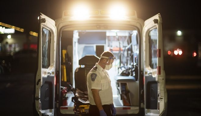 An EMT pauses for a moment while loading a stretcher back into an ambulance after dropping off a patient at a newly opened field hospital operated by Care New England for COVID-19 patients in Cranston, R.I, Tuesday, Dec. 1, 2020. (AP Photo/David Goldman)
