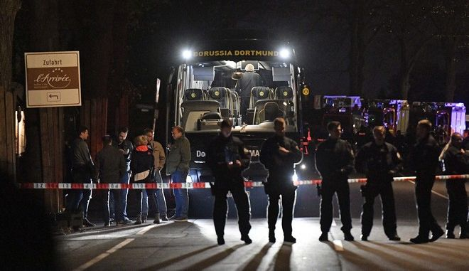 Police officers stand in front of Dortmund's damaged team bus after an explosion before the Champions League quarterfinal soccer match between Borussia Dortmund and AS Monaco in Dortmund, western Germany, Tuesday, April 11, 2017.  (AP Photo/Martin Meissner)