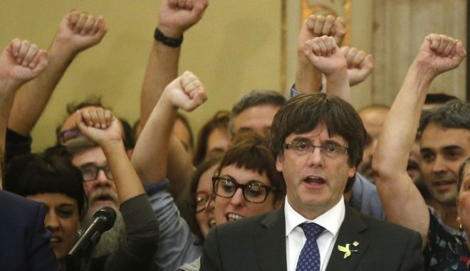 FILE- In this Friday, Oct. 27, 2017 file photo, Catalan President Carles Puigdemont sings the Catalan anthem inside the parliament after a vote on independence in Barcelona, Spain. Pro-independence Catalans are cheering the regional parliament's declaration of secession from Spain, a country they don't regard as their own. (AP Photo/Manu Fernandez, File)