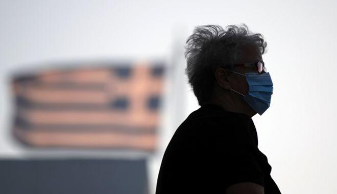 Ηλικιωμένη με μάσκα έξω από εκκλησία