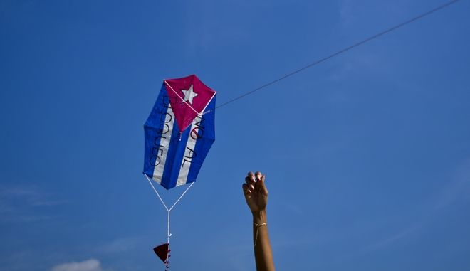 """A child flies a kite with the colors of the Cuban flag and a text written on it in Spanish that reads """"Against the embargo"""" during an activity to request the end of the United States embargo against Cuba, in Havana, Cuba, Saturday, Feb. 18, 2017. (AP Photo/Ramon Espinosa)"""