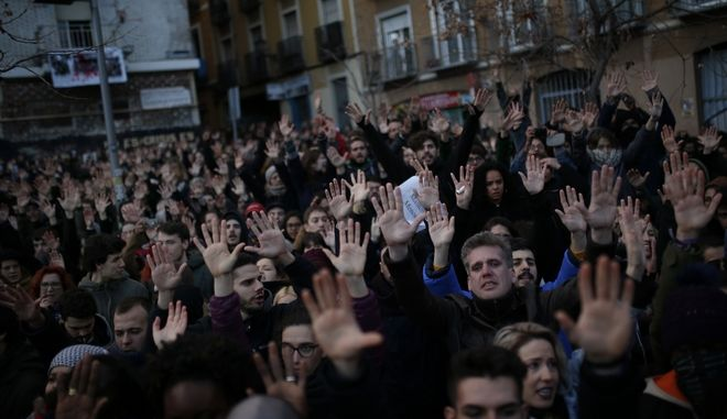 People raise their hands during a protest after the death of a Senegalese street vendor at the Lavapies neighborhood in Madrid, Friday, March 16, 2018. Spain's capital is grappling with the aftermath of violent unrest following the death of an African street vendor who had been running away from police officers. (AP Photo/Francisco Seco)